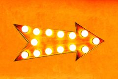Orange, yellow and reddish color vintage bright and colorful illuminated metallic display arrow sign on orange wall Stock Images