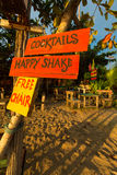 Orange and yellow signs on the beach offering cocktails and chai Stock Images