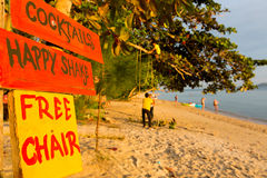 Orange and yellow signs on the beach offering cocktails and chai Stock Photography