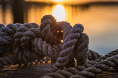 Orange and yellow sky above harbor port sunset rope Stock Images