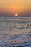 Orange yellow Sun sunsets over blue clear sky on the open sea 2. Orange yellow Sun sunsets over blue clear sky on the open sea Stock Photo