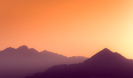 Orange and yellow sunset above layers of mountains. Stock Photo