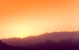 Orange and yellow sunset above layers of mountains. Stock Images