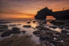 Orange and Yellow Sunset Skies over Grey Seashore Rocks and Calmed Ocean Royalty Free Stock Image