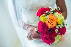 Orange, yellow, white wedding bouquet. Beautiful orange, red, and yellow bouquet loaded with daisies and roses in the hands of a beautiful ethnic bride Stock Photos