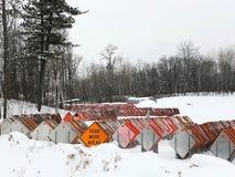 Orange Zeichen der STRASSENARBEITEN VORAN unter Dutzenden Verkehrsschildern in einem schneebedeckten Los stockfotos