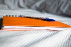 Orange Zeitschriftennotizbuch mit Stift auf Bett lizenzfreie stockfotografie