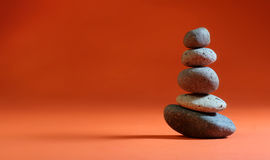 Orange Zen Stack. Five Zen Stones stacked over warm orange background Stock Photography