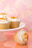 Orange Zest Cupcakes. Sponge cupcakes with butter cream frosting and orange zest topping on white stand Royalty Free Stock Images