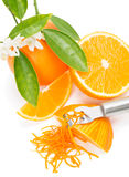 Orange with a zest. Orange fruit with leaves and blossom, orange zest with zester   on a white background, top view Royalty Free Stock Photography
