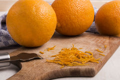 Orange zest on wooden board with zester Royalty Free Stock Photos