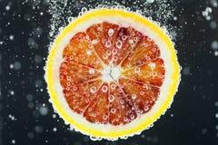 Orange Zitrusfruchtscheibe, die in Wasser fällt Stockfoto