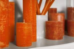 Orange zylinderförmige Kerzen auf einem Regalwohnungsdekor Stockfotos