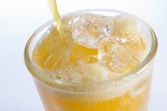 Orangeade de derramamento em um vidro do gelo fotografia de stock royalty free