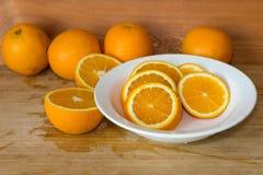 Orangen auf einer Tabelle und auf einer weißen Platte Stockfoto