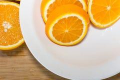 Orangen auf einer Tabelle und auf einer weißen Platte Lizenzfreies Stockfoto