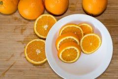 Orangen auf einer Tabelle und auf einer weißen Platte Stockfotos