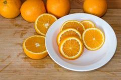Orangen auf einer Tabelle und auf einer weißen Platte Lizenzfreie Stockfotos