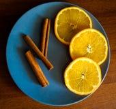 Orangen auf grauer Platte mit Zimtstangen Stockfotos