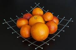 Orangen auf Metallplatte auf schwarzem Hintergrund Stockfotografie