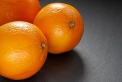 Orangen auf Schieferhintergrund lizenzfreie stockbilder