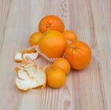 Orangen in den kleinen Papierkörben auf hölzerner Beschaffenheit mit Tangerinen Stockfotos