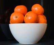 Orangen in der weißen Schüssel mit einem schwarzen Hintergrund Lizenzfreies Stockbild