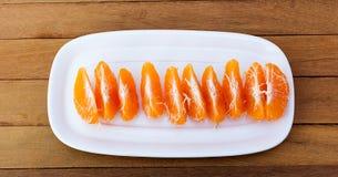 Orangen, die auf Platte auf dem Bretterboden abgezogen werden Stockfoto