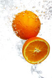 Orangen fielen in Wasser stockbild