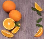 Orangen ganz und in tadellose Bl?tter auf einem h?lzernen Beschaffenheitshintergrund schneiden lizenzfreies stockfoto