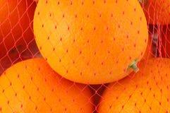 Orangen im Ineinander greifenbeutel Stockfoto