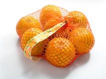 Orangen im Plastikmaschensack auf weißem Hintergrund Stockfoto