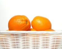 Orangen im weißen Korb Stockbilder