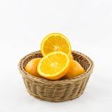 Orangen im Weidenkorb lokalisiert Lizenzfreie Stockfotos