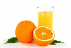 Orangen mit Blättern und frischem Saft Stockbild