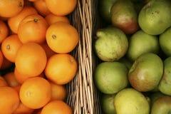 Orangen und Äpfel in den Körben Stockbilder