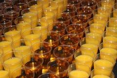 Orangen- und Apfelsaftgetränke in den Plastikbechern Lizenzfreie Stockfotos