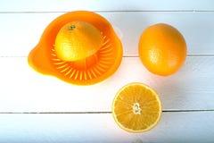 Orangen und auf einem hölzernen Brett auf einem weißen hölzernen Hintergrund Stockfoto