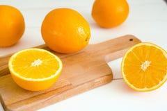 Orangen und auf einem hölzernen Brett auf einem weißen hölzernen Hintergrund Stockfotografie