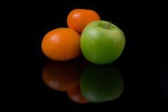 Orangen und ein Apfel Stockbild