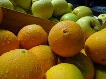 Orangen und grüner Apfel im Vordergrund Stockfotos