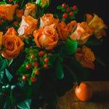 Orangen und orange Rosen auf Holztisch Stockbild