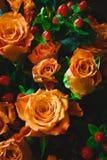 Orangen und orange Rosen auf Holztisch Stockfotografie