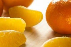 Orangen und orange Scheiben auf einem hellen Holztisch Stockfotos
