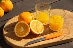 Orangen und Orangensaft auf dem Tisch Lizenzfreie Stockfotos