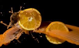 Orangen und Orangensaft spritzen auf einem schwarzen Hintergrund Stockfoto