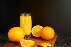 Orangen und Saft auf schwarzem Hintergrund lizenzfreies stockfoto