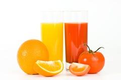 Orangen- und Tomatefrüchte mit Saft im Glas, Stockfotografie