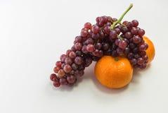 Orangen und Trauben auf weißem Hintergrund Stockfotos