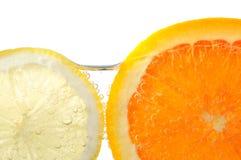 Orangen- und Zitronescheiben im Wasser Stockfotos